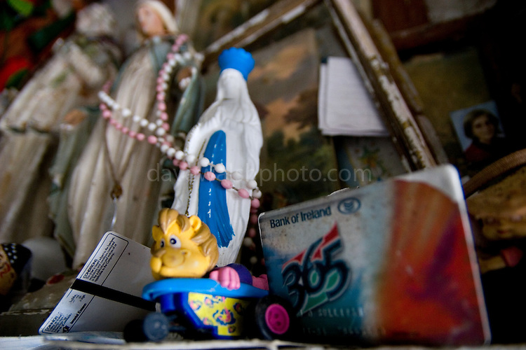 """Toys and bank card - connection?....On the Liscannor -  Doolin road, near the Cliffs of Moher, this ostensibly holy well is full of wonderful, decaying votive offerings. St. Brigid never actually existed in Christian times - in mythology she was the """"exalted one"""" - daughter of the Dagda and therefore one of the Tuatha De Danann.....The """"cave"""" at St. Brigit's Well is full of strange objects. Decaying statues, rotting dolls, faded masscards, abandoned prosthetic limbs, rosary beads, toys, polaroid photographs. All left as mementos, blessings, prayers for the dead, the ill and the future."""