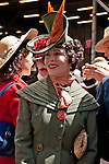 Woman in a vintage green suit with a large vintage hat with orange feathers in the Easter Parade on 5th Avenue in New York City