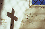 Shadow of crucifix on peeling white paint of niche with blue sky seen through diamond-leaded window