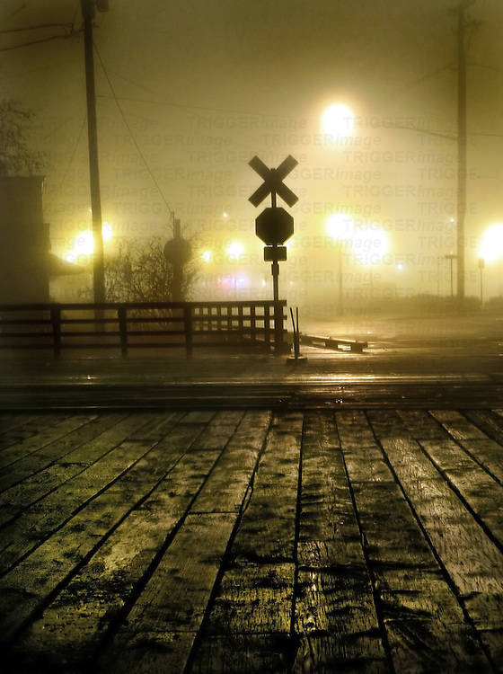 Fog at a rail crossing with street lights in the distance