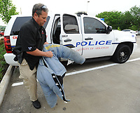 NWA Democrat-Gazette/ANDY SHUPE<br /> Cpl. Chris Krodell of the University of Arkansas Police Department shows the holes in the Handler Protection Training suit that he and other K-9 officer handlers use to train that is in need of replacement Thursday, April 20, 2017, during an evening of fundraising for the department at Whataburger on Martin Luther King Jr. Boulevard in Fayetteville. The department is raising money to support the K-9 division including the purchase of a new Handler Protection Training suit for training.