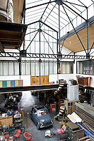 Light floods into this huge converted factory from the glass roof of the studio
