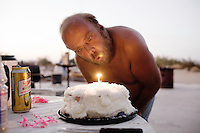 Niland, California, August 2, 2008 - With the temperature hoveing around 105 degrees at 9:30 in the evening, Willie Reynolds blows the candle out on his birthday cake that has melted from the summer heat.