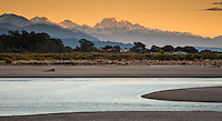 View of Mt. Cook and Mt. Tasman at sunset from Hokitika River mouth, South Westland, West Coast, New Zealand