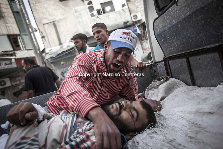 A Syrian civilian bawls for the dead body of his relative shot in the cross fire as he takes it at the back of a truck for its buring outside of one hospital in Tarik Al-Bab neighborhood, at the northeast of Aleppo City.