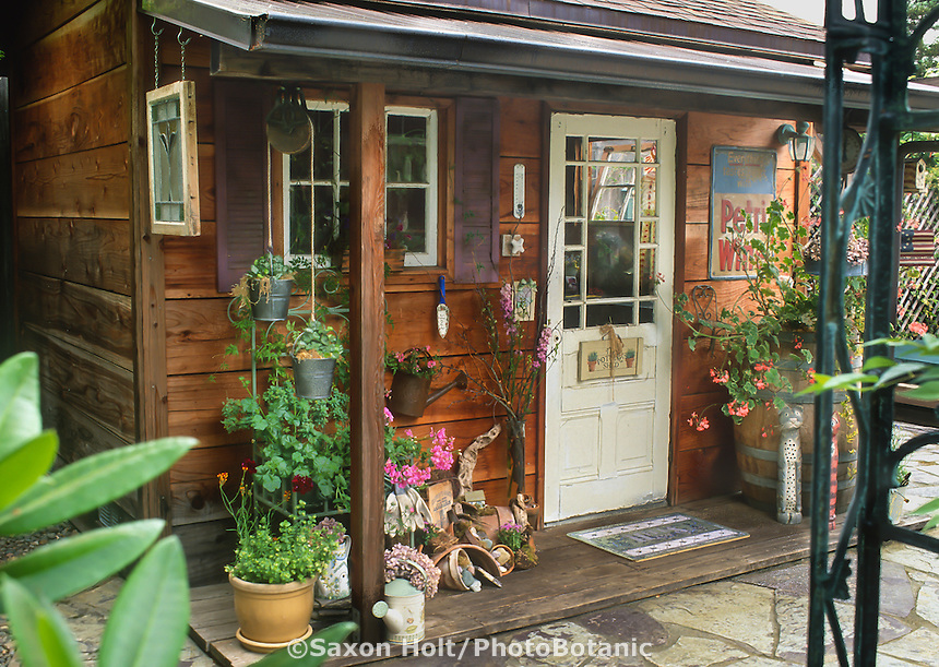 Rustic country garden potting shed decorated with bric-a-brac and flea market finds and boardwalk mini porch