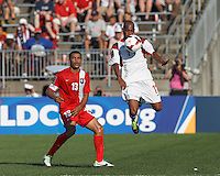 Cuban midfielder Ariel Martinez (11) traps the ball as Belize defender Dalton Eiley (13) closes. In CONCACAF Gold Cup Group Stage, the national team of Cuba (white) defeated national team of Belize (red), 4-0, at Rentschler Field, East Hartford, CT on July 16, 2013.