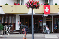 Switzerland. Canton Bern. Interlaken. Life on a Sunday afternoon. A couple with an umbrella walks on the pavement. An elderly tourist man is seated close to a sculpture at the Bernerhof hotel's main entrance. A plastic cow stands in front of hotel. An arabic muslim woman from the Middle East is seated on her room's balcony. She has covered her hair with a hijab. A swiss flag is on display on the building's wall. The flag of Switzerland consists of a red flag with a white cross (a bold, equilateral cross) in the centre. It is one of only two square sovereign-state flags. 31.07.2016 © 2016 Didier Ruef