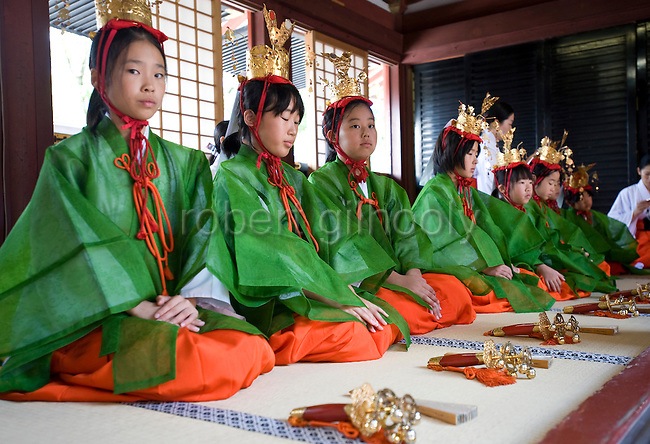 """Young """"yaotome"""" female performers kneel in an antechamber during a ritual in the main hall of Tsurugaoka Hachimangu shrine during the second day of the 3-day Reitaisai grand festival in Kamakura, Japan on  15 Sept. 2012.  Photographer: Robert Gilhooly"""