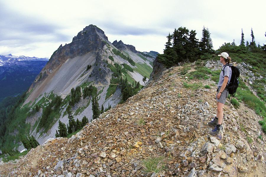 Woman hiking on ridge with Pinnacle Peak in background, Mount Rainier National Park, Cascade Mountains, Washington