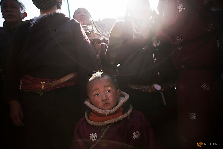 A boy joins other ethnic Tibetan people praying as the sun comes out from behind the hill above a Buddhist laymen lodge where thousands of monks and nuns gather for morning chanting session during the Utmost Bliss Dharma Assembly, the last of the four Dharma assemblies at Larung Wuming Buddhist Institute in remote Sertar county, Garze Tibetan Autonomous Prefecture, Sichuan province, China November 1, 2015. The eight-day gathering of people chanting mantras and listening to teachings of monks starts every year around the 22rd of the ninth month on Tibetan calendar, the great day of Buddha's Descending from Tushita Heavens. The Larung Wuming Buddhist Institute, located some 3700 to 4000 metres above the sea level was founded in 1980 by Khenpo Jigme Phuntsok, an influential lama of Nyingma sect of Tibetan buddhism with only around 30 students but is now widely known as one of the biggest centres to study Tibetan Buddhism in the world. Picture taken November 1, 2015.  REUTERS/Damir Sagolj