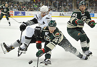 Iowa Wild center Warren Peters, center, upends San Antonio Rampage center Ryan Martindale, left, after a faceoff, as Iowa center Zack Phillips looks on, during an AHL hockey game, Saturday, Jan. 25, 2014, in San Antonio. Iowa won 2-1 in overtime. (Darren Abate/AHL)