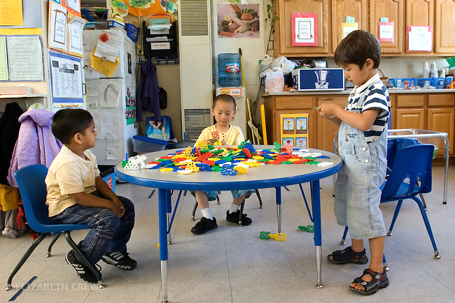 Berkeley CA  Four-year-olds exhibiting parallel and onlooker play at construction toy table at bilingual, Spanish-English preschool