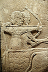 Picture & image of a Neo-Hittite orthostat with a chariot Releif sculpture from Karkamis,, Turkey. Ancora Archaeological Museum. The Cahiot is pulled by horses with plumed headresses. One man os about to shoot an arrow from his bow, the other man is driving the cahriot. Below the horse is a animal cowering. 6