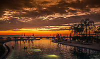 Fine Art Photograph. Sunset on Banderas Bay, Puerto, Vallarta, Mexico. Silhouette The Grand Venitian Pool with people in the pool looking at the golden rays of the setting sun.