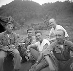 Officers of the Second Infantry Division relax for a group photo while drinking their beer ration in a break from Korean WAr fighting. Members of the 2nd Infantry Division during the Korean War in 1950 or 1951.