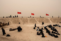Female relatives of men killed during the Iran - Iraq War (1980 - 1988) offer prayers at a memorial site near the Iraqi border. Thousands of Iranians travel annually on Rahian-e Nour (Travellers of the Path of Light) Tours. They are usually female relatives paying respects to their dead fathers, husbands and sons.