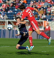 Leaping New England forward Zack Schilawski (15) attempts to play the ball while being pressured by Chicago defender Josip Mikulic (23).  The Chicago Fire defeated the New England Revolution 3-2 at Toyota Park in Bridgeview, IL on Sept. 25, 2011.
