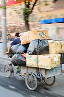 Man pedaling tricycle filled with stacked boxes, Beijing, China, Asia