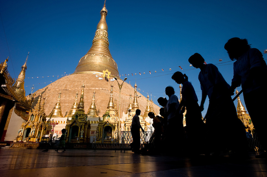 Volunteers form ranks to sweep the terrace surrounding the historic Shwedagon Paya in Yangon, Unuon of Myanmar (Burma), Nov. 26, 2009. The broom brigades clean the marble terrace several times a day. The Shwedagon pagoda's central hti, an umbrella spire atop the giant zedi structure, sports a 76-karat diamond that casts red, green white beams to specific spots on the terrace as the sun rises or sets. The massive complex sits atop a 190-foot hill accessed by four stair-stepped walkways guarded by 30-foot-tall mythical half-lion half-dragon creatures called chinthe. The central 98-foot-tall zedi is surrounded by an incredible assortment of other smaller zedi, statues and temples...EDS: Not for syndication nor redistribution. Web slide show only. Please do not strip metadata for Web use.