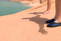 young adult couple making shadows on red sandstone on shore of lake Powell