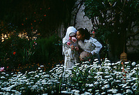 Novices stop and smell flowers in a garden during a break from their prayers and work at Santa Catalina Convent in Peru. Built in 1580 and enlarged in the 17th century, now 30 cloistered nuns live in privacy in the convent.  Five are novicias who study for five years to become a nun. The youngest nun is 15 and the oldest is 98. <br />
