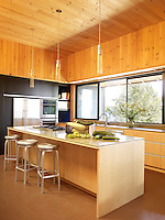 A simple, contemporary kitchen finished with natural pine panelling on the walls and ceiling