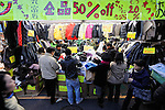 Bargain hunters look through cut-price goods at a sportswear store in  the Ameyokocho market area in Tokyo. Ameyokocho, which has long been known for its bargain basement prices, is experiencing a boom recently with shoppers increasingly seeking quality goods at low prices amid Japan's continuing recession. Photographer: Robert Gilhooly