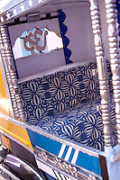 The seat of the rickshaw has been upholstered in a geometric blue and white fabric