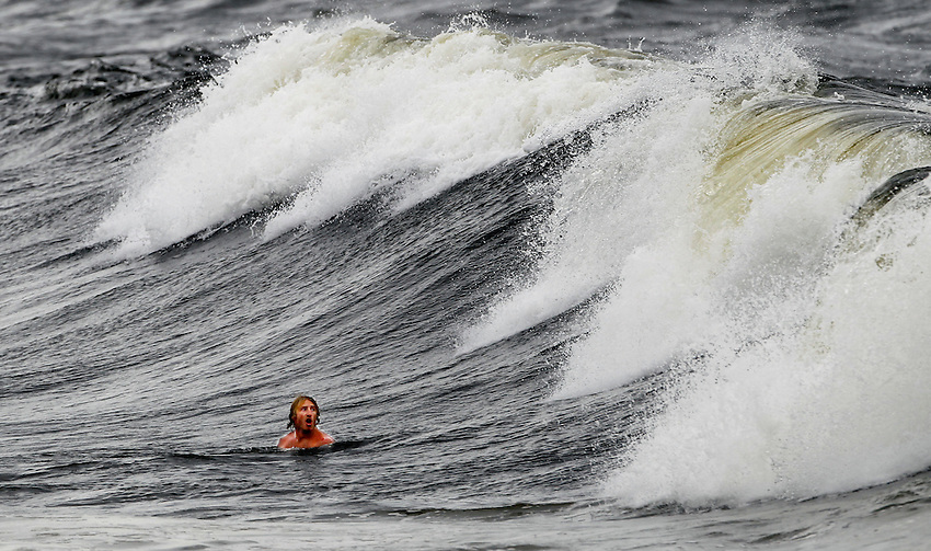 Manasquan lifeguard Eric Roberts eyes an approaching wave as borough lifeguards work out in 3-4 foot surf as Hurricane Irene approaches the Jersey Shore.  Manasquan's beachfront was evacuated at 6 am today.