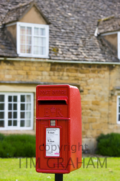 Old postbox in front of traditional village cottages in Willersey, The Cotswolds, Worcestershire, UK