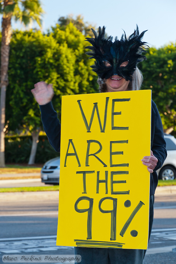 """Laurel stands on a corner holding a yellow """"We are the 99%"""" sign at the Occupy Orange County Irvine camp.  I took this on Halloween, hence the costume."""