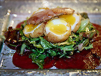 Appetizer presentation with quail eggs, prosciutto, fresh greens and thinly sliced beets