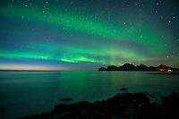 Northern Lights - Aurora Borealis shine in sky over sea and mountains, Storsandnes, Flakstadøy, Lofoten Islands, Norway