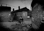 Young boy rides his bicycle through a garbage strewn alleyway in residential compound built directly beneath smokestacks which emit particulates that coat every surface of the neighborhood with toxic soot, central Wuhai, Inner Mongolia, China.
