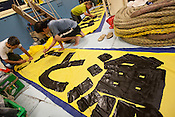 Daisuke Miyachi, Sakyo Noda and Emma Briggs painting banners on board the Greenpeace ship Rainbow Warrior, as it transits northwards to Fukushima, Japan, on Monday 25th April 2011.