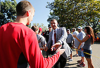 Ohio State Buckeyes head coach Urban Meyer shakes hands with fans as the team walks from St. John Arena to Ohio Stadium before the Ohio State football season opener against Buffalo at in Columbus, Saturday afternoon, August 31, 2013. (Columbus Dispatch  / Eamon Queeney)