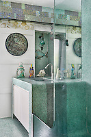 A detail of a blue and white bathroom tiled in mosaic tiles. A washbasin is set in a cupboard unit with a mirror above.