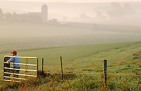 Agricultural landscape of a farmer looking out over a pasture in foggy weather.