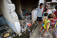 Children playing amidst rubbish and waste, Tallo, Makassar, Sulawesi, Indonesia.