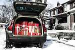 Car standing in a driveway near a house with a trunk full of Christmas gifts