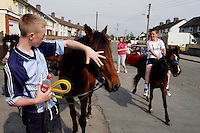 Youths pictured riding their ponies on a sunny day in the suburb of Finglas, Dublin, Ireland.<br />