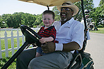 Champions Tour veteran Jim Thorpe gives two-year-old Jake Noonan a ride on his golf cart before his round in the Allianz Pro-Am in Des Moines, Iowa.   Jake is the son of Danny Noonan who is caddying this week for Doug Johnson.