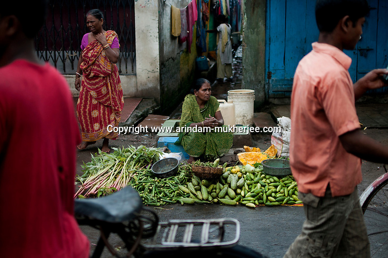 Madhabi Tiwari (54) selling vegitables at Dakkhin Dari slum market. After her husband's death 4 years ago she was in huge economic crisis when Bandhan helped her by helping her set up a vegitable stall under their CSP program. This is a program run by Bndhan NGO the not for profit wing of Bandhan Micro finance. Since then she is a regular money borrower from Bandhan. Kolkata, West Bengal, India. Arindam Mukherjee