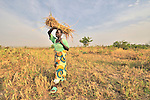 Peresi Nyoka brings home grass she has cut to use on the thatched roof of her hut in Yei, Southern Sudan. Ms. Nyoka is a United Methodist.