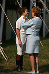 A woman adjusts the  collar of a groom as she prepares horses before four in hand coaching event in Locust, New Jersey.