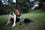 Die Autorin Eva Lezzi studiert auf der Wiese.