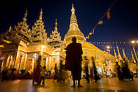An elderly monk meditates before the historic Shwedagon Paya, Yangon, Unuon of Myanmar (Burma), Nov. 26, 2009. The Shwedagon pagoda's central hti, an umbrella spire atop the giant zedi structure, sports a 76-karat diamond that casts red, green white beams to specific spots on the terrace as the sun rises or sets. The massive complex sits atop a 190-foot hill accessed by four stair-stepped walkways guarded by 30-foot-tall mythical half-lion half-dragon creatures called chinthe. The central 98-foot-tall zedi is surrounded by an incredible assortment of other smaller zedi, statues and temples...EDS: Not for syndication nor redistribution. Web slide show only. Please do not strip metadata for Web use.