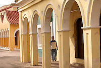 Man walking under portales or colonnade in the Spanish colonial river town of Tlacotalpan, Veracruz, Mexico. Tlacotlapan was made a UNESCO World Heritage Site in 1998.