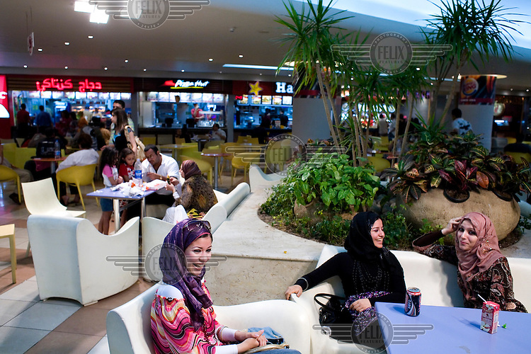 Three fashionable young women laugh as they sit together at a cafe table in a shopping centre.
